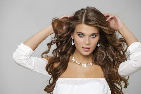 Beauty portrait de jeune femme séduisante aux cheveux, isolé sur fond gris