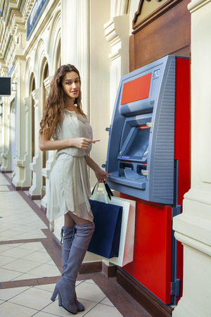 cash slips: Brunette young lady using an automated teller machine . Woman withdrawing money or checking account balance Stock Photo