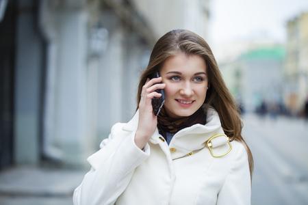 bata blanca: Retrato de feliz chica morena joven en la capa blanca que habla en el tel�fono al aire libre del resorte