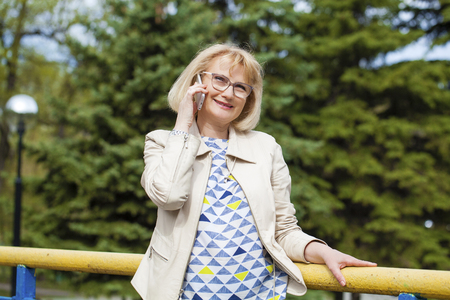 telephone call: Mature beautiful blonde woman is calling on a cell phone, outdoors in spring park