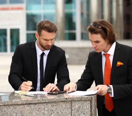testament schreiben: Business people sign a contract, street outdoors