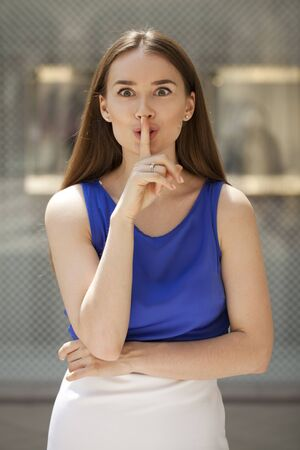 forefinger: Young beautiful brunette woman has put forefinger to lips as sign of silence, against shop window