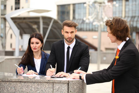 testament schreiben: Business people sign a contract, street outdoors