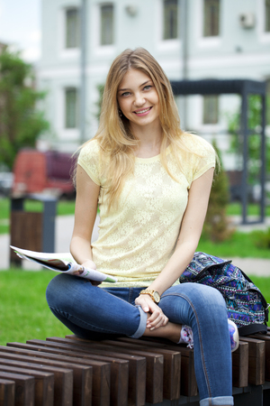 young womens: Young beautiful blonde girl reading a womens magazine sitting on a bench in the summer park