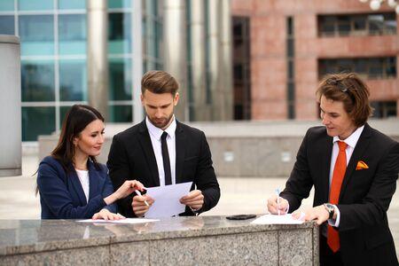 testament schreiben: Gesch�ftsleute, die einen Vertrag unterzeichnen, Stra�e im Freien Lizenzfreie Bilder