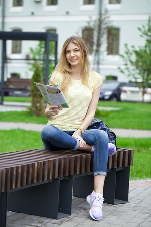 Young beautiful blonde girl reading a womens magazine sitting on a bench in the summer park