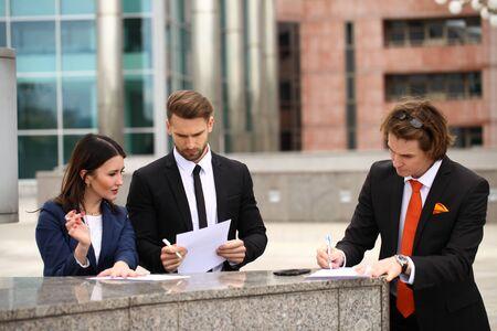 testament schreiben: Geschäftsleute, die einen Vertrag unterzeichnen, Straße im Freien Lizenzfreie Bilder