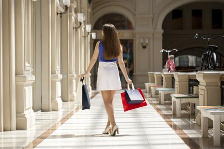 Jonge mooie brunette vrouw met een aantal boodschappentassen in het winkelcentrum