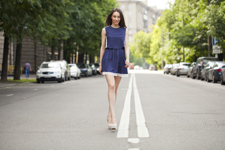 Portrait in full growth, young beautiful brunette woman in a blue short dress walking on the road, summer street outdoors