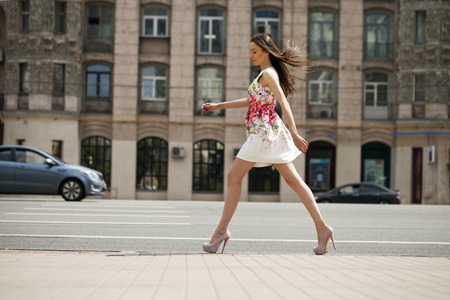 sexual: Portrait in full growth, young beautiful brunette woman in white flowers dress walking on the street, summer outdoors