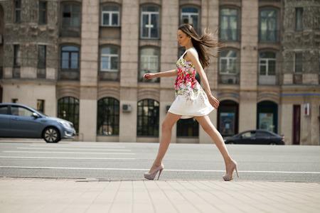 gente adulta: Retrato en pleno crecimiento, mujer morena hermosa joven en flores vestido blanco caminando en la calle, verano al aire libre