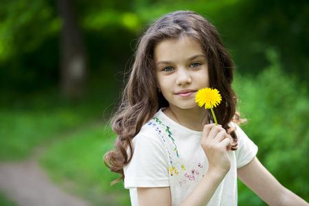 niños rubios: Niña que huele un diente de león amarillo en el parque de la primavera Foto de archivo