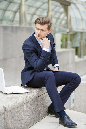 interactivity: Portrait of a young successful businessman with a laptop in front of office building