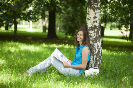 european white birch: Young beautiful woman leafing through a magazine while sitting in the summer park