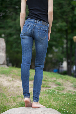 bare waist: Back view of a long women legs posing with blue jeans, summer outdoors Stock Photo
