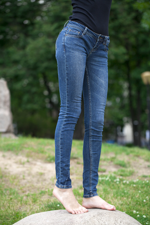 tight fit: Front view of a long women legs posing with blue jeans, summer outdoors Stock Photo