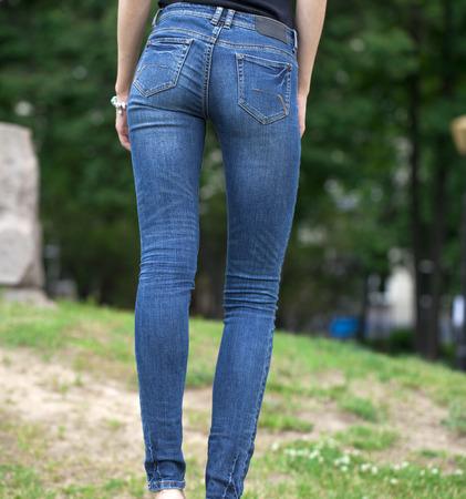 jeans apretados: Vista posterior de un largo piernas de las mujeres posando con los pantalones vaqueros azules, verano al aire libre Foto de archivo