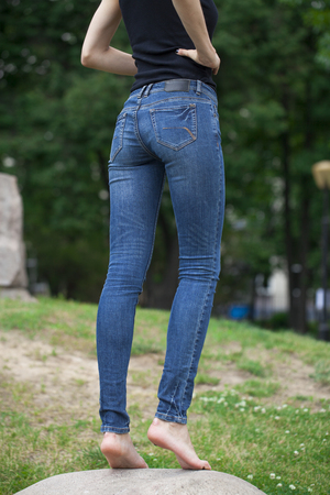 girls bottom: Back view of a long women legs posing with blue jeans, summer outdoors Stock Photo