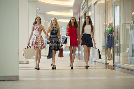four people: Group of happy smiling women shopping with colored bags walking in the mall
