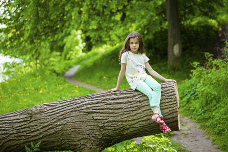 Little Girl in white dress sitting on tree trunk on the background of summer park Stock Photo