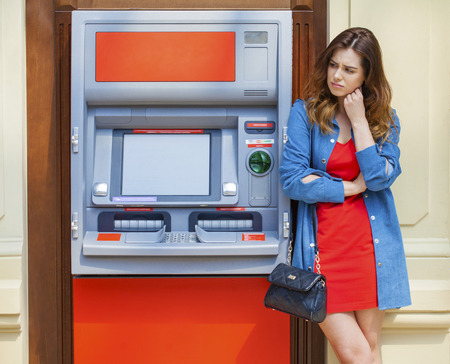 cash slips: Frustrated young woman stands on against ATM in a shopping center