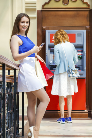 cash slips: Young happy brunette woman withdrawing money from credit card at ATM  Stock Photo