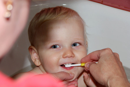 hair tuft: Baby boy brushing his teeth sitting in the bath Stock Photo