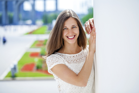 Closeup portrait of a happy young brunette woman smiling, summer street outdoors
