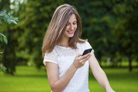 Young Woman texting on the smart phone walking in the summer park Stock Photo