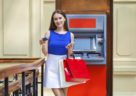 cash money: Young happy brunette woman withdrawing money from credit card at ATM, indoor shop