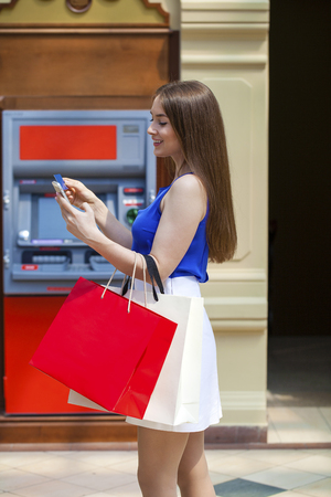 withdrawing: Young happy brunette woman withdrawing money from credit card at ATM, indoor shop