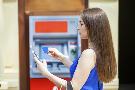 pin code: Young happy brunette woman withdrawing money from credit card at ATM, indoor shop