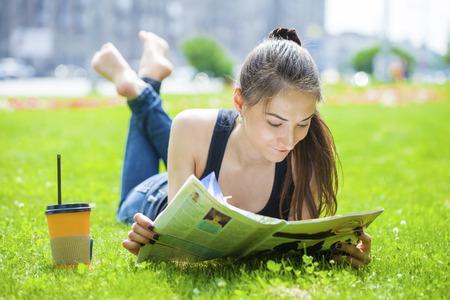Junge schöne Frau, Brunette, der eine Frauenzeitschrift auf dem grünen Rasen im Sommer Park lesen