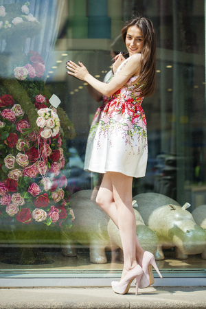shopfront: Portrait in full growth, young beautiful brunette woman in white flowers dress walking on the street, summer outdoors