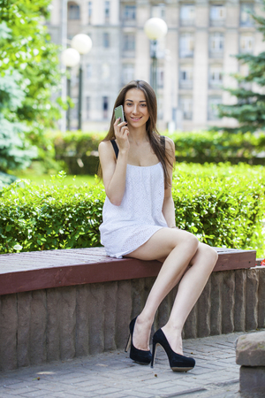 female legs: Beautiful young brunette woman calling by phone, summer park outdoors
