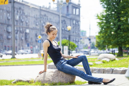 brown haired: Young beautiful brown haired woman in blue jeans sitting on stone in summer street