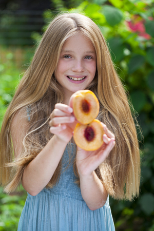 blonde little girl: Portrait of a young blonde little girl with peach, summer outdoor Stock Photo