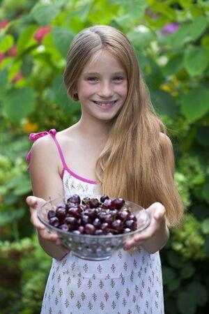 blonde little girl: Beautiful blonde little girl holding a bowl of cherries in the garden