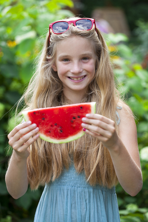 Portrait of a young blonde little girl with watermelon, summer outdoor Stock Photo