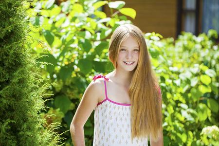 blonde little girl: Portrait of a beautiful young blonde little girl on the background of summer park