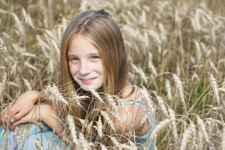 blonde little girl: Portrait of a beautiful blonde little girl on the background of wheat field Stock Photo