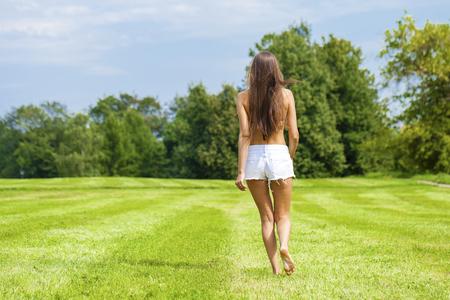 Glücklicher Brunette Frau auf Sommer oder Frühling Wiese läuft