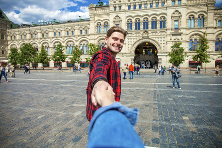 Follow Me. Young happy guy pulls the girls hand on the Red Square, Russian Moscow