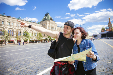 Happy tourists sightseeing city with map. Red Square, Moscow, Russia