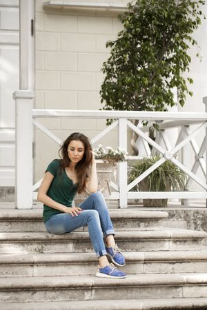brown haired: Young beautiful brown haired woman in blue jeans sitting on stone steps
