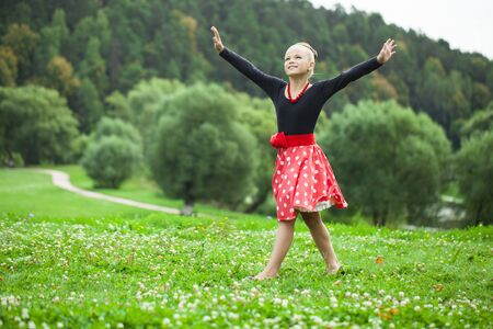 pretty dress: Happy Little girl in a beautiful dress dancing on a lawn in a summer park Stock Photo