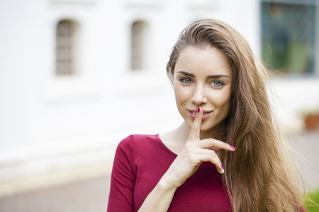 forefinger: Young beautiful brunette woman has put forefinger to lips as sign of silence, outdoors