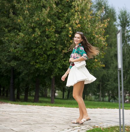 Young happy brunette woman in white skirt and blouse, summer park outdoors Stock Photo