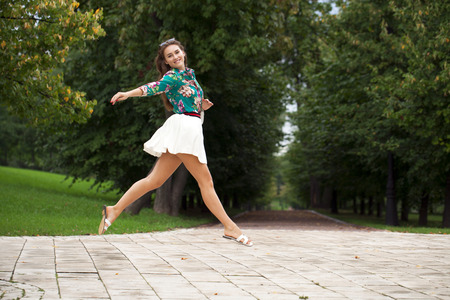 steins: Young happy brunette woman in white skirt and blouse walking in the summer park