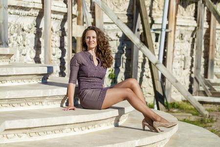 mujeres morenas: Retrato en pleno crecimiento, joven bella mujer morena en traje marrón sentado en los escalones de piedra